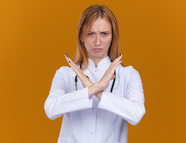 Frowning young female ginger doctor wearing medical robe and stethoscope doing no gesture