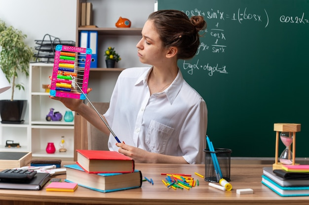 Frowning young female math teacher sitting at desk with school supplies holding and looking at abacus pointing at it with pointer stick in classroom
