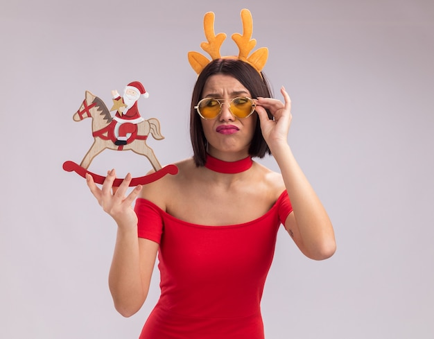 Frowning young girl wearing reindeer antlers headband and glasses holding and looking at santa on rocking horse figurine grabbing glasses isolated on white background
