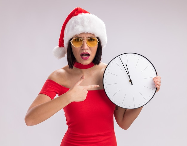 Ragazza accigliata che indossa cappello da babbo natale e occhiali che tengono e puntano all'orologio guardando la telecamera isolata su sfondo bianco