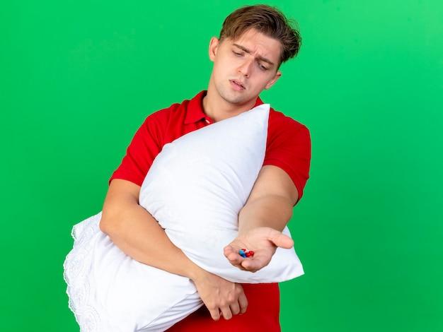 緑の壁に隔離されたカプセルを見て枕と医療カプセルを保持している若いハンサムな金髪の病気の男