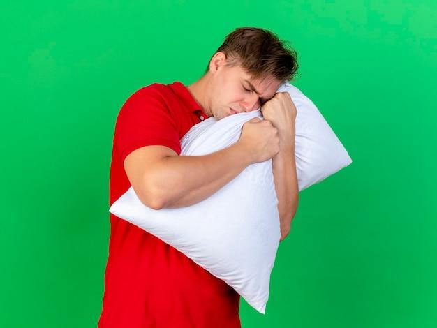 Accigliato giovane uomo malato biondo bello che abbraccia cuscino con gli occhi chiusi isolato sulla parete verde