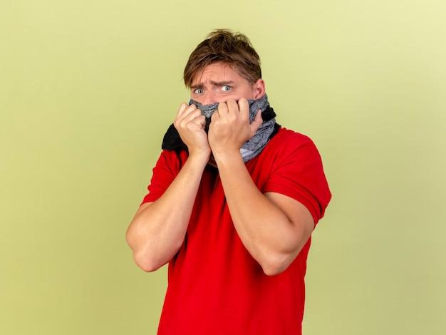 眉をひそめている若いハンサムな金髪の病気の男は、オリーブグリーンの壁に隔離された正面を見てスカーフで口を覆うスカーフを身に着けています