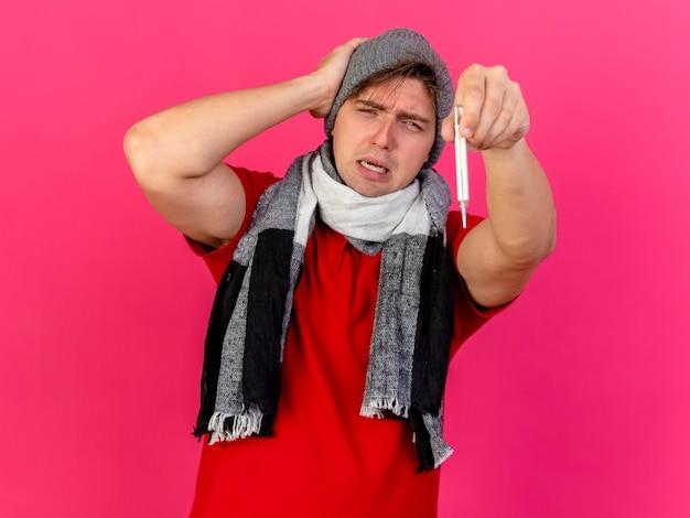 Хмурый молодой красивый блондин больной мужчина в зимней шапке и шарфе, протягивающий термометр вперед, держа руку на голове, глядя вперед, изолированный на розовой стене