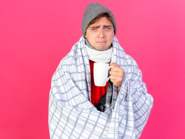 Accigliato giovane uomo malato biondo bello che indossa cappello invernale e sciarpa avvolto in una tazza di tè della holding del plaid isolato sulla parete rosa