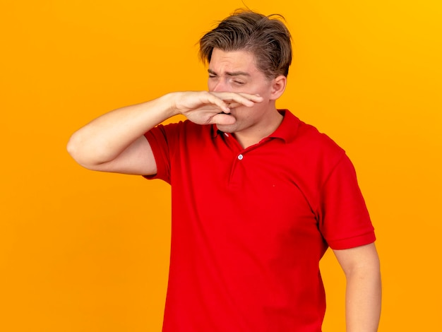 Frowning young handsome blonde ill man wiping his nose with hand with closed eyes isolated on orange wall
