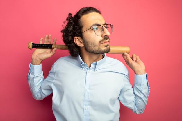 진홍색 벽에 고립 된 측면을보고 목 뒤에 야구 방망이 들고 안경을 쓰고 찡그림 젊은 잘 생긴 백인 남자