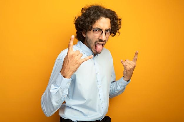 Хмурый молодой красивый кавказский мужчина в очках, смотрящий в камеру, показывает язык, делающий рок-знаки, изолированные на оранжевом фоне с копией пространства
