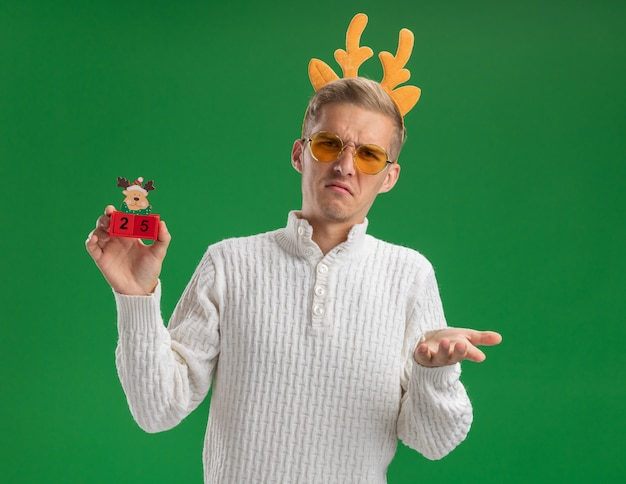 Frowning young handsome guy wearing reindeer antlers headband with glasses holding christmas tree toy with date looking at camera showing empty hand isolated on green background