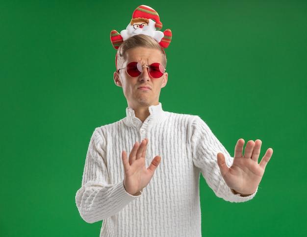 Accigliato giovane bel ragazzo che indossa la fascia di babbo natale con gli occhiali guardando a lato facendo gesto di rifiuto isolato su sfondo verde