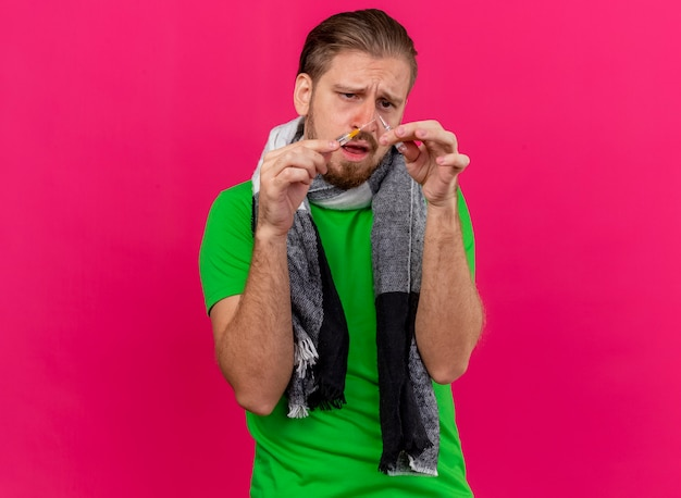 ピンクの壁に隔離された注射器とアンプルを保持しているスカーフを身に着けている若いハンサムな病気の男を眉をひそめている