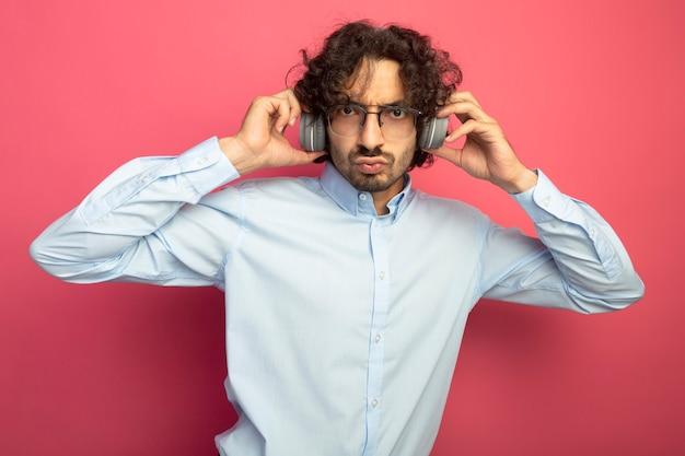 Accigliato giovane uomo bello con gli occhiali e le cuffie guardando le cuffie afferrando anteriori isolate sul muro rosa