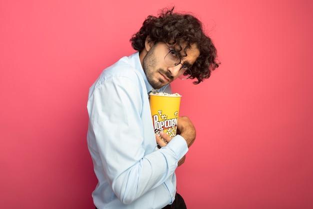 Accigliato giovane uomo bello con gli occhiali in piedi in vista di profilo tenendo il secchio di popcorn guardando davanti isolato sul muro rosa