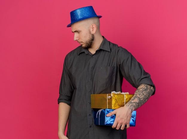 Accigliato giovane ragazzo bello partito che indossa il cappello del partito che tiene confezioni regalo guardando lato isolato sul muro rosa