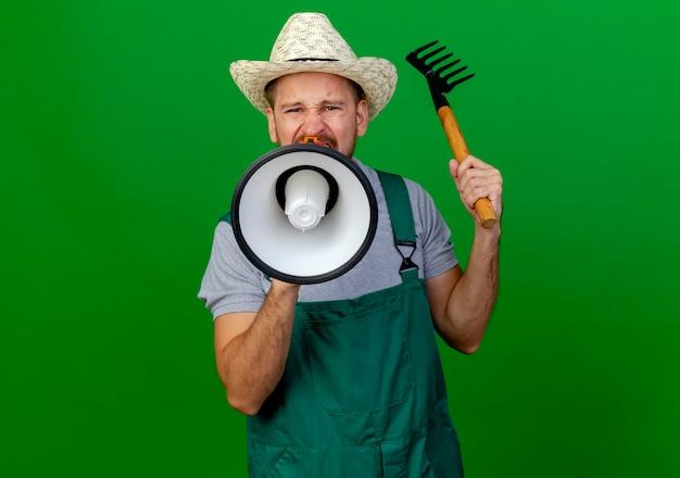 制服を着た若いハンサムなスラブの庭師を眉をひそめ、熊手を保持し、スピーカーで話している帽子を探しています