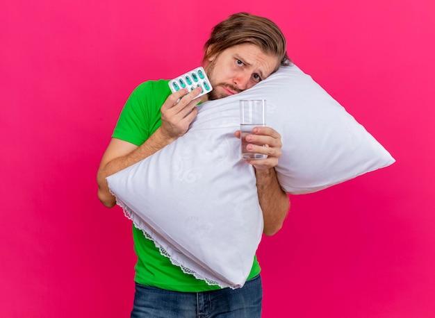 Хмурый молодой красивый славянский больной обнимает подушку, глядя на переднюю упаковку капсул и стакан воды, изолированные на розовой стене с копией пространства