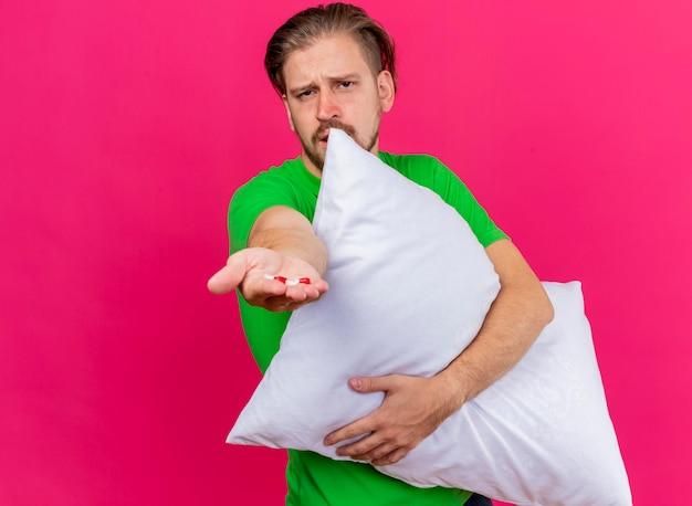 Accigliato giovane bello slavo malato abbracciando il cuscino che allunga le capsule verso la parte anteriore guardando davanti isolato sulla parete rosa con lo spazio della copia