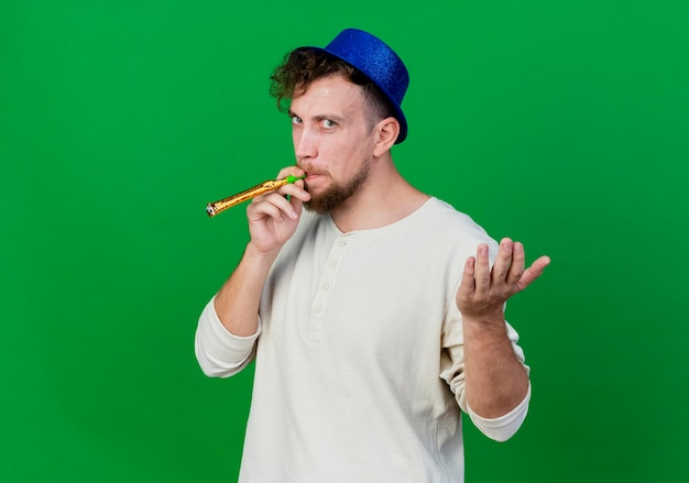 Frowning young handsome slavic party guy wearing party hat blowing party blower looking at front showing empty hand isolated on green wall with copy space