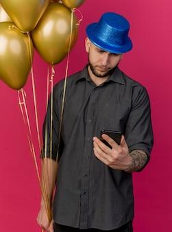 ピンクの壁に隔離された電話を見て風船と携帯電話を保持しているパーティーハットを身に着けている若いハンサムなスラブパーティー男