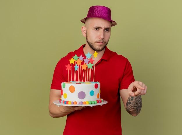찡그린 젊은 잘 생긴 슬라브 파티 사람을 찾고 생일 케이크를 들고 복사 공간 올리브 녹색 배경에 고립 된 측면을 가리키는 파티 모자를 쓰고