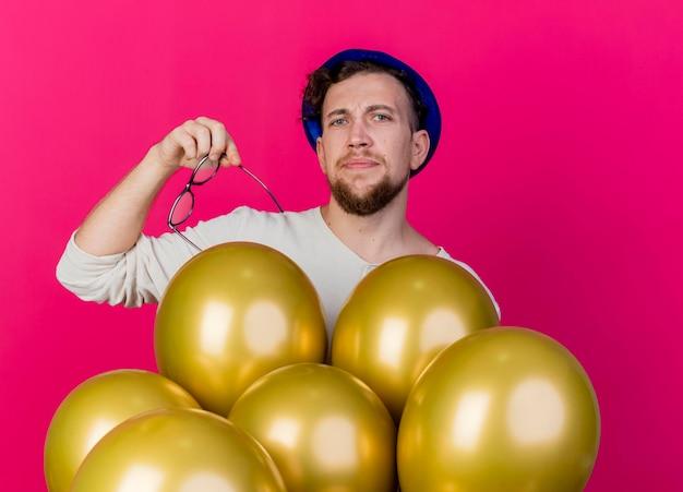 皱着眉头年轻英俊的斯拉夫党人佩带的党帽子拿着玻璃和站立在看前面的气球后的气球隔绝在桃红色墙壁后