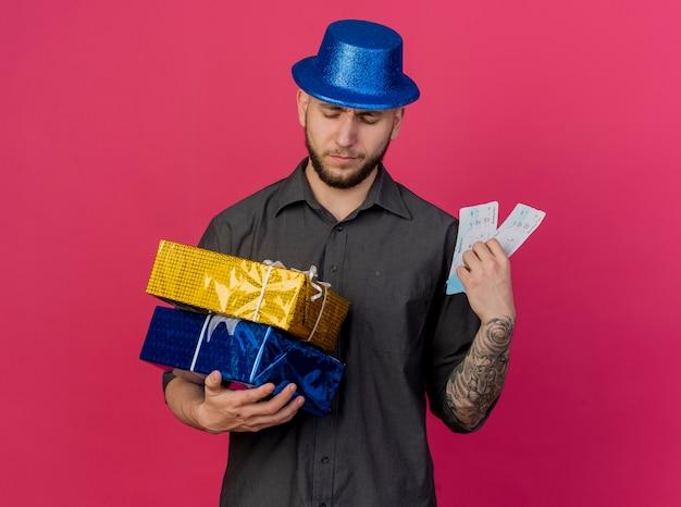 Accigliato giovane bel partito slavo ragazzo che indossa il cappello del partito che tiene e guardando confezioni regalo in possesso di biglietti aerei isolati su sfondo cremisi