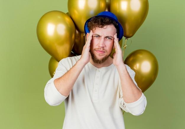 올리브 녹색 벽에 고립 된 두통으로 고통을 머리에 손을 유지 앞에보고 풍선 앞에 서있는 파티 모자를 쓰고 찡그림 젊은 잘 생긴 슬라브 파티 남자