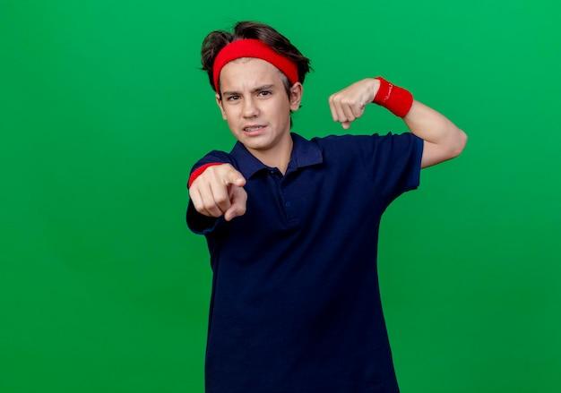 강한 제스처를 찾고 및 복사 공간이 녹색 벽에 고립 앞에 poiting 치과 교정기와 머리띠와 팔찌를 착용하는 젊은 잘 생긴 스포티 한 소년을 찡그림