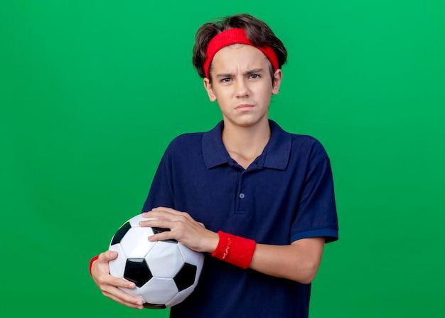 복사 공간 녹색 벽에 고립 된 전면을보고 축구 공을 들고 치과 교정기와 머리띠와 팔찌를 착용하는 젊은 잘 생긴 스포티 한 소년을 찡그림