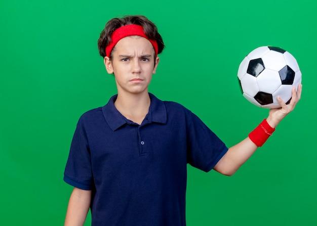 녹색 벽에 고립 된 전면을보고 축구 공을 들고 치과 교정기와 머리띠와 팔찌를 착용하는 젊은 잘 생긴 스포티 한 소년을 찡그림