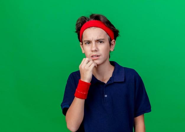 복사 공간이 녹색 벽에 고립 된 전면 감동 턱을보고 치과 교정기와 머리띠와 팔찌를 착용하는 젊은 잘 생긴 스포티 한 소년을 찡그림