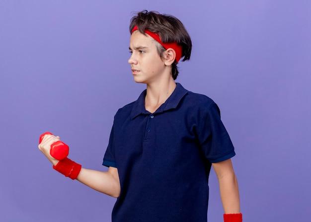 Хмурый молодой красивый спортивный мальчик с головной повязкой и браслетами с зубными скобами, смотрящий в сторону, держащую гантель, изолированную на фиолетовой стене Бесплатные Фотографии