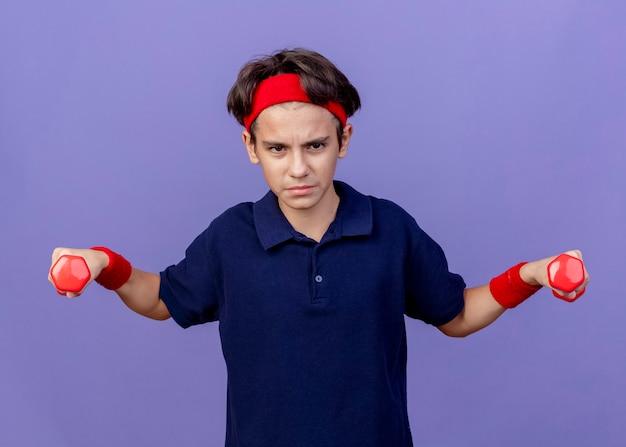 紫色の壁に隔離されたダンベルをまっすぐに保持している歯科用ブレースとヘッドバンドとリストバンドを身に着けている若いハンサムなスポーティな男の子