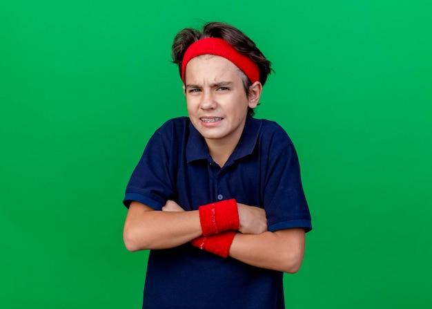 복사 공간이 녹색 벽에 고립 된 전면을보고 닫힌 자세로 서 치과 교정기와 머리띠와 팔찌를 착용하는 젊은 잘 생긴 스포티 한 소년을 찡그림