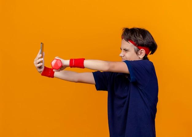 オレンジ色の壁に隔離された自撮り写真を撮ってダンベルを伸ばして歯列矯正器でヘッドバンドとリストバンドを身に着けている若いハンサムなスポーティな男の子を育てる