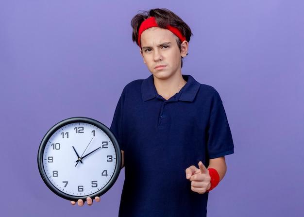 Accigliato giovane ragazzo sportivo bello che indossa la fascia e braccialetti con bretelle dentali che tengono l'orologio che indica e isolato sulla parete viola con lo spazio della copia