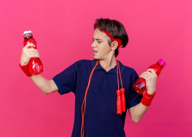 Accigliato giovane ragazzo sportivo bello che indossa fascia e braccialetti con bretelle dentali e corda per saltare intorno al collo tenendo e guardando le bottiglie d'acqua isolate sul muro cremisi