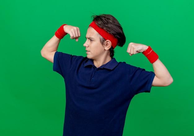 Accigliato giovane ragazzo sportivo bello che indossa la fascia e braccialetti con bretelle dentali guardando al lato facendo un gesto forte isolato sulla parete verde