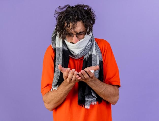 보라색 벽에 고립 된 닫힌 눈으로 의료 약을 들고 안경과 스카프를 착용하는 젊은 아픈 남자를 찡그림