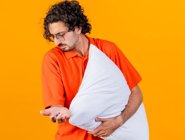 Хмурый молодой больной человек в очках держит медицинские капсулы и подушку, глядя вниз, изолированные на оранжевой стене