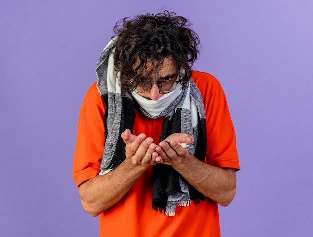 Accigliato giovane uomo malato con gli occhiali e sciarpa che tiene e guardando pillole mediche isolate sulla parete viola