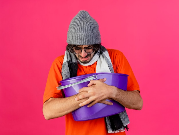 Хмурый молодой больной человек в очках, зимняя шапка и шарф, держащий пластиковое ведро, с тошнотой, смотрящий вниз, изолированный на розовой стене