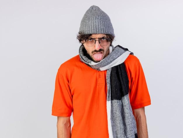 흰색 벽에 고립 된 혀를 보여주는 전면을보고 안경 겨울 모자와 스카프를 착용하는 젊은 아픈 남자를 찡그림