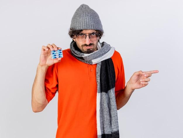 白い壁に隔離された側を指している正面を見てカプセルのパックを示す眼鏡の冬の帽子とスカーフを身に着けている眉をひそめている若い病気の男