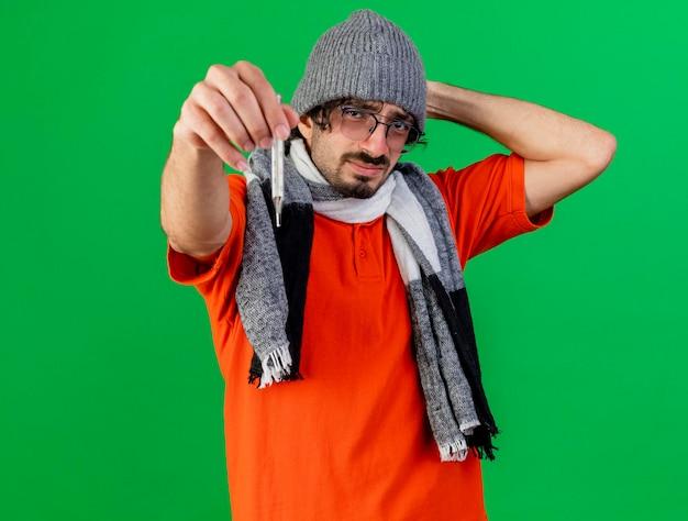 眼鏡の冬の帽子とスカーフを身に着けている若い病気の男がコピースペースで緑の壁に隔離された正面を見て頭の後ろに手を保ちながら温度計を正面に伸ばして