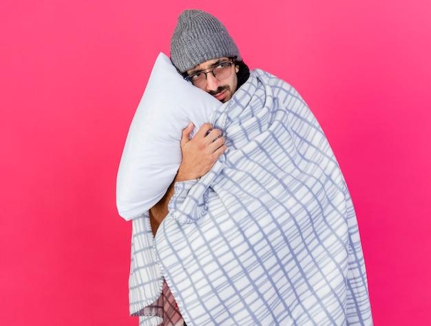 분홍색 벽에 고립 된 측면을보고 그것으로 얼굴을 만지고 격자 무늬 지주 베개에 싸여 안경 겨울 모자와 스카프를 착용하는 젊은 아픈 남자를 찡그림 무료 사진