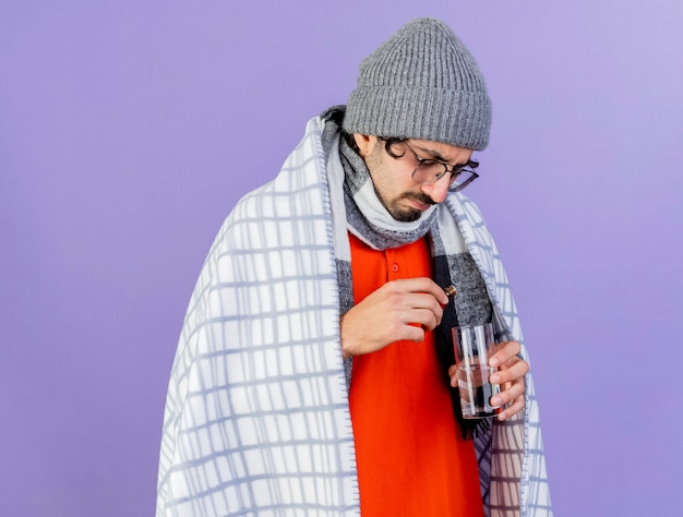 紫色の壁に隔離された水のガラスにガラスの格子縞の注ぐ薬に包まれたガラスの冬の帽子とスカーフを身に着けている若い病気の男を育てる