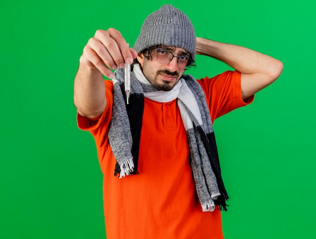 Frowning young ill man wearing glasses winter hat and scarf stretching out thermometer towards front keeping hand behind head looking at front isolated on green wall with copy space