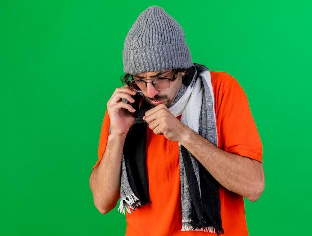 Accigliato giovane uomo malato con gli occhiali cappello invernale e sciarpa parlando al telefono mantenendo il pugno vicino alla bocca tossendo guardando in basso isolato sul muro verde con spazio di copia