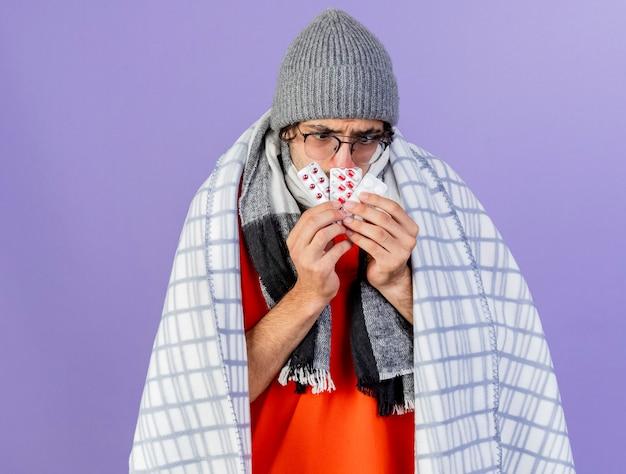 Accigliato giovane uomo malato con gli occhiali cappello invernale e sciarpa avvolti in un plaid che tiene confezioni di pillole mediche davanti alla bocca guardandoli isolati sul muro viola